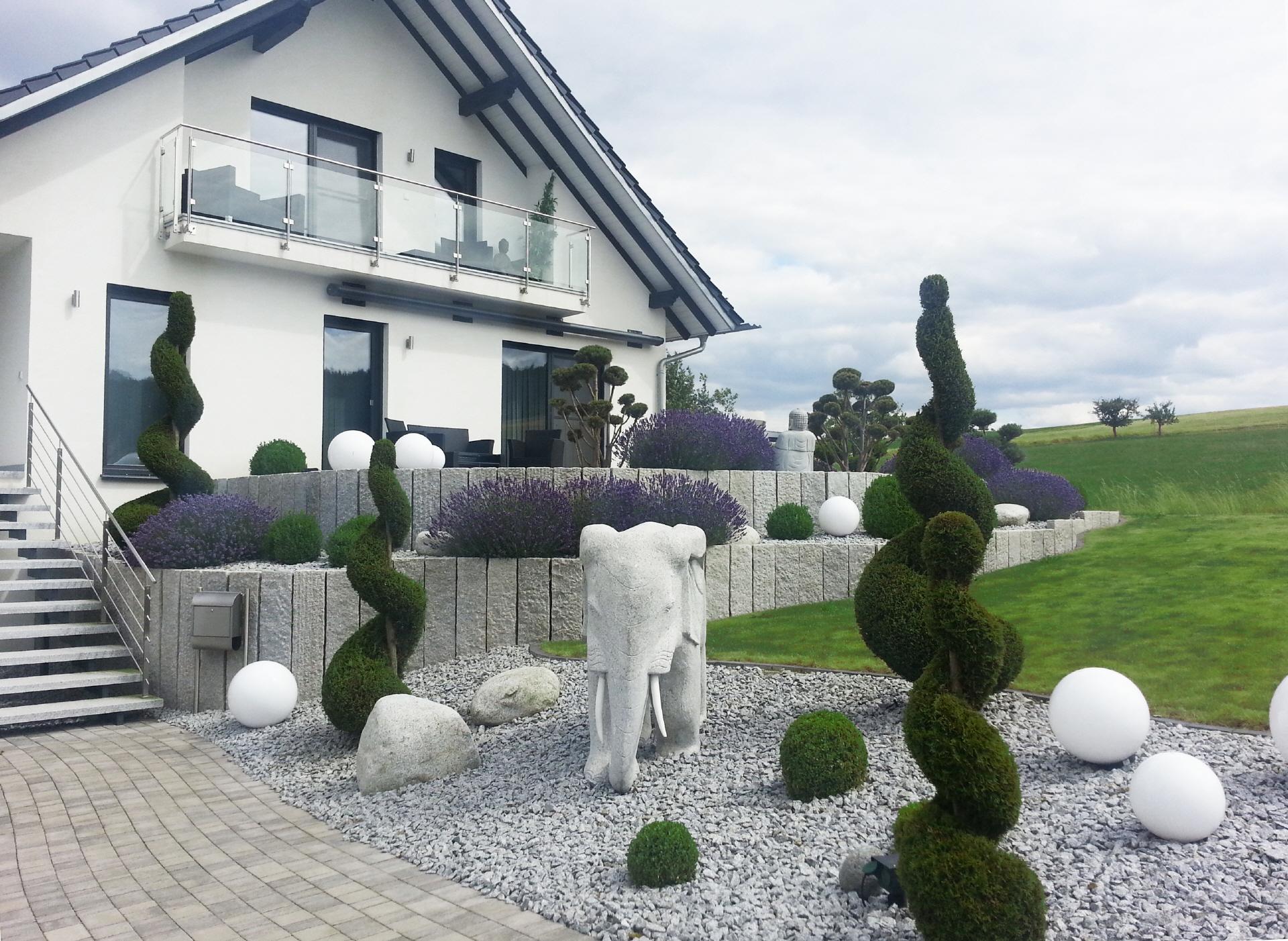 Moderner Garten mit Steinfiguren und Formschnitt